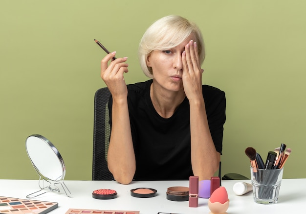 Zadowolona młoda piękna dziewczyna siedzi przy stole z narzędziami do makijażu, trzymając eyeliner zakryte oko ręką odizolowaną na oliwkowozielonej ścianie