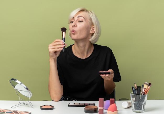 Zadowolona młoda piękna dziewczyna siedzi przy stole z narzędziami do makijażu, trzymając i dmuchając pudrowy rumieniec na oliwkowozielonej ścianie