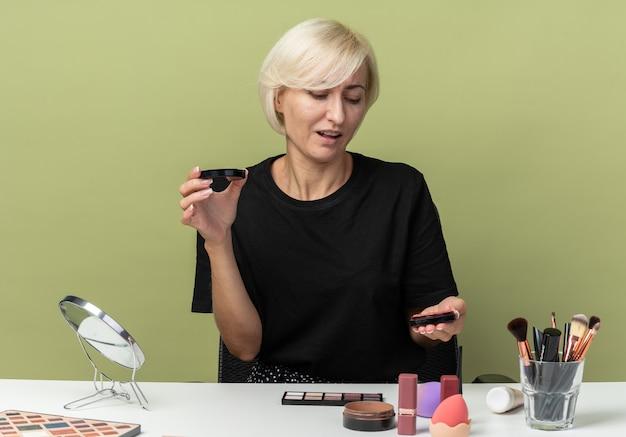 Zadowolona młoda piękna dziewczyna siedzi przy stole z narzędziami do makijażu, trzymając i patrząc na rumieniec w proszku na oliwkowo-zielonej ścianie