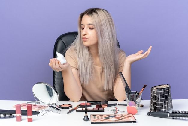 Zadowolona młoda piękna dziewczyna siedzi przy stole z narzędziami do makijażu, trzymając krem do włosów na niebieskiej ścianie