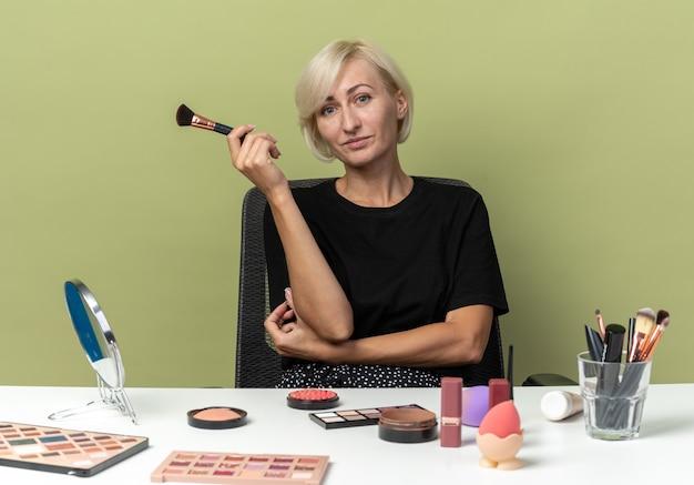 Zadowolona młoda piękna dziewczyna siedzi przy stole z narzędziami do makijażu, trzymając pędzel do proszku na oliwkowozielonej ścianie