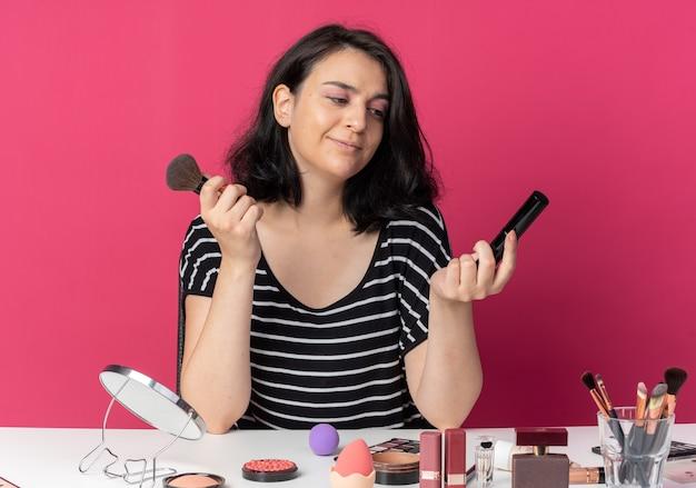 Zadowolona młoda piękna dziewczyna siedzi przy stole z narzędziami do makijażu, trzymając pędzel do pudru z tuszem do rzęs na różowej ścianie