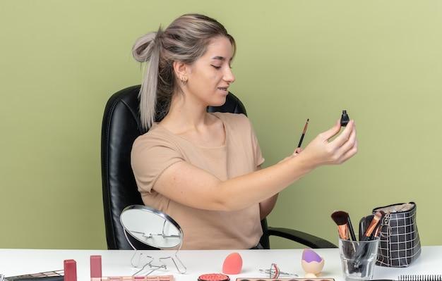 Zadowolona młoda piękna dziewczyna siedzi przy stole z narzędziami do makijażu trzymając tusz do rzęs w aparacie odizolowana na oliwkowozielonej ścianie