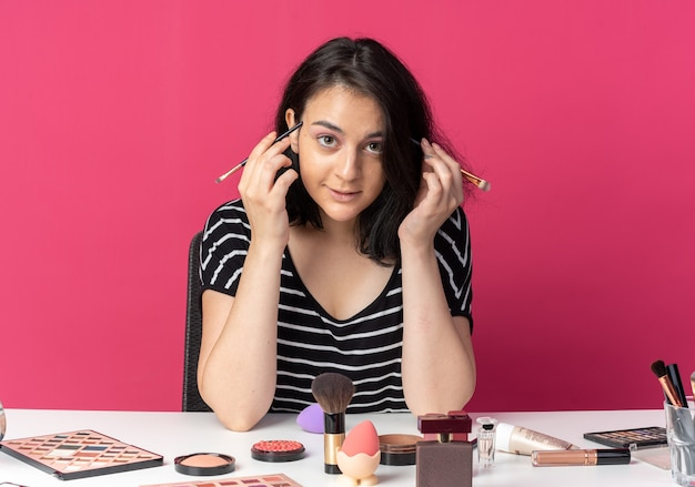 Zadowolona młoda piękna dziewczyna siedzi przy stole z narzędziami do makijażu trzymającymi pędzle do makijażu twarzy na różowej ścianie