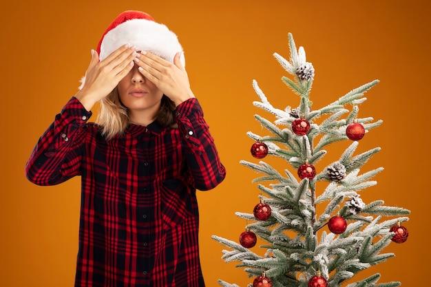Zadowolona młoda piękna dziewczyna stojąca w pobliżu choinki w świątecznym kapeluszu zakrytym oczami z rękami na białym tle na pomarańczowym tle