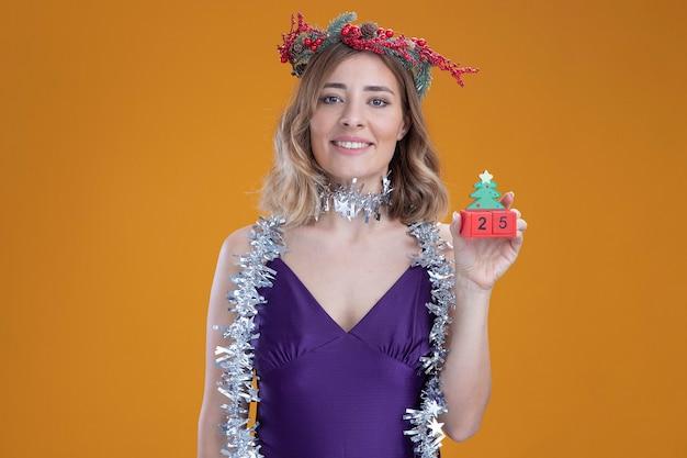 Zadowolona młoda piękna dziewczyna ubrana w fioletową sukienkę i wieniec z girlandą na szyi, trzymająca świąteczną zabawkę odizolowaną na brązowym tle
