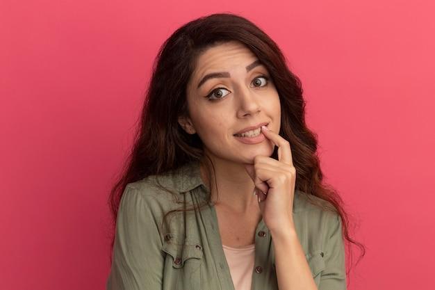Zadowolona młoda piękna dziewczyna ubrana w oliwkową koszulkę kładąc palec na ustach na białym tle na różowej ścianie
