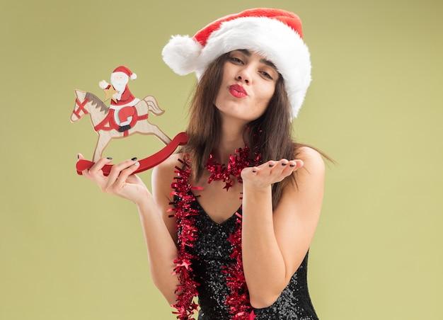 Zadowolona młoda piękna dziewczyna ubrana w świąteczny kapelusz z girlandą na szyi, trzymająca świąteczną zabawkę pokazującą gest pocałunku odizolowaną na oliwkowozielonym tle