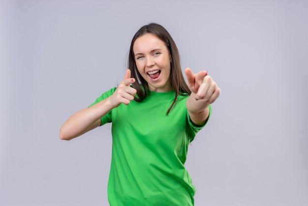 Zadowolona młoda piękna dziewczyna ubrana w zieloną koszulkę wyszła i szczęśliwa, wskazując palcami na aparat, uśmiechając się radośnie stojąc na białym tle