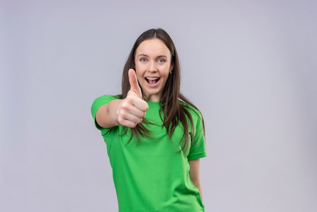 Zadowolona młoda piękna dziewczyna ubrana w zielony t-shirt uśmiechając się radośnie pokazując kciuki stojąc na białym tle