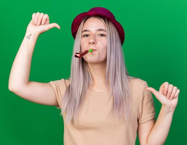 Zadowolona młoda piękna dziewczyna w czapce imprezowej dmuchająca na siebie gwizdkami na imprezę