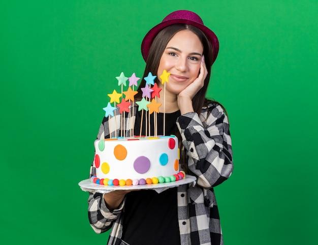 Zadowolona młoda piękna dziewczyna w imprezowym kapeluszu, trzymająca ciasto, kładąc dłoń na policzku