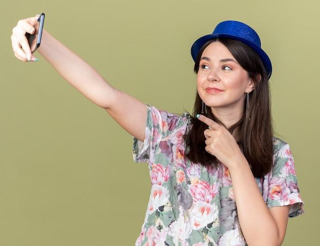 Zadowolona młoda piękna dziewczyna w kapeluszu imprezowym bierze punkty selfie na telefon odizolowany na oliwkowozielonej ścianie