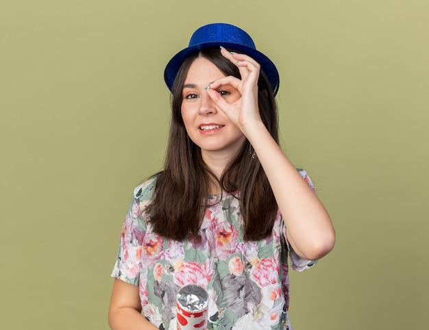 Zadowolona młoda piękna dziewczyna w kapeluszu imprezowym trzymająca armatę konfetti pokazującą gest wyglądający na oliwkowozielonej ścianie