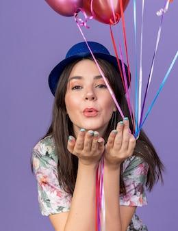 Zadowolona młoda piękna dziewczyna w kapeluszu imprezowym, trzymająca balony pokazujące gest pocałunku na niebieskiej ścianie