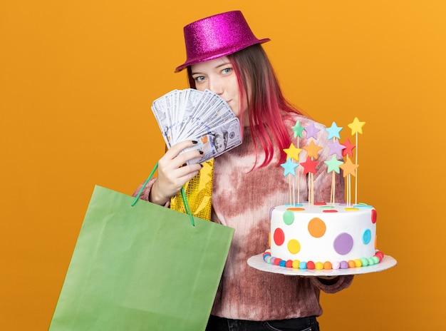 Zadowolona młoda piękna dziewczyna w kapeluszu imprezowym trzymająca ciasto z torbą na prezenty pokrytą twarzą gotówką