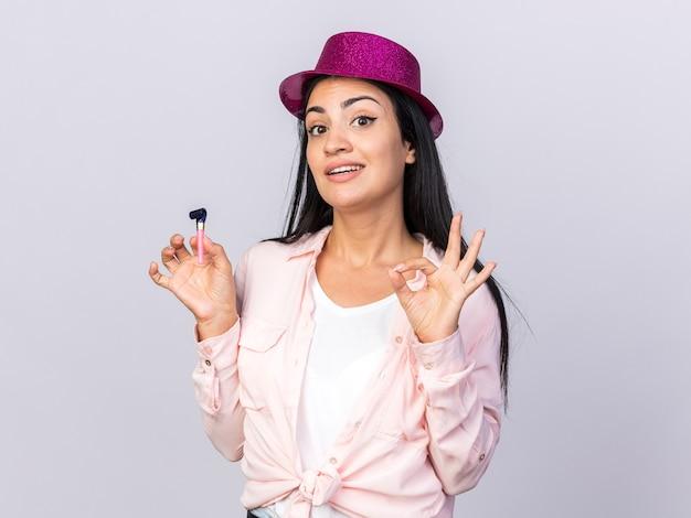 Zadowolona młoda piękna dziewczyna w kapeluszu imprezowym trzymająca gwizdek pokazujący w porządku gest na białym tle na białej ścianie