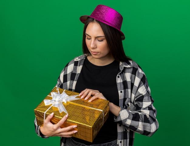 Zadowolona młoda piękna dziewczyna w kapeluszu imprezowym, trzymająca i patrząca na pudełko na białym tle na zielonej ścianie
