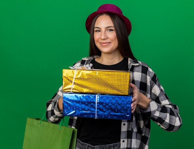 Zadowolona młoda piękna dziewczyna w kapeluszu imprezowym, trzymająca pudełka na prezenty z torbą na prezenty