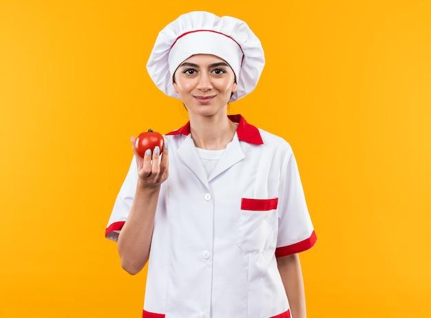 Zadowolona młoda piękna dziewczyna w mundurze szefa kuchni trzymająca pomidora na pomarańczowej ścianie