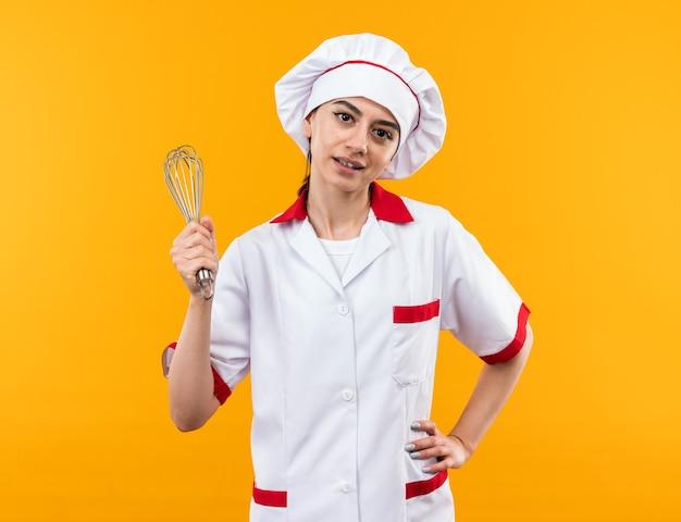 Zadowolona młoda piękna dziewczyna w mundurze szefa kuchni trzymająca trzepaczkę, kładąc rękę na biodrze