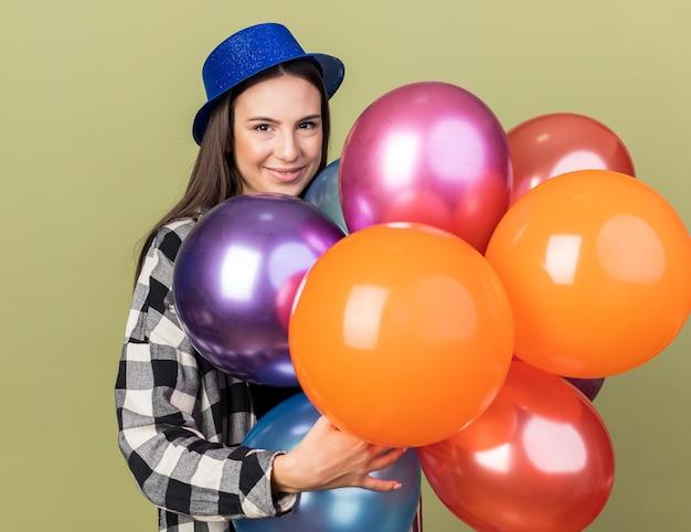 Zadowolona młoda piękna dziewczyna w niebieskim kapeluszu, trzymając balony