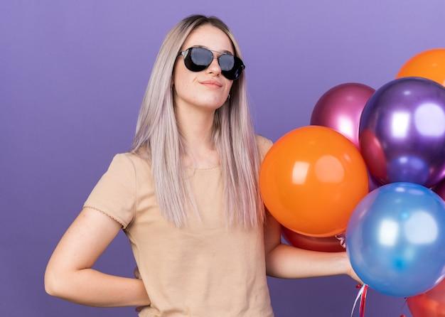 Zadowolona młoda piękna dziewczyna w okularach, trzymająca balony, kładąc rękę na biodrze
