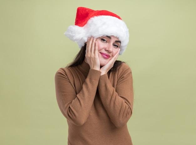Zadowolona młoda piękna dziewczyna w świątecznym kapeluszu zakrytym policzkami z rękami odizolowanymi na oliwkowozielonej ścianie
