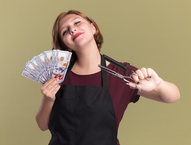 Zadowolona młoda piękna kobieta fryzjerka w fartuchu pokazuje gotówkę trzymając grzebień do włosów i nożyczki, patrząc pewnie stojąc nad zieloną ścianą