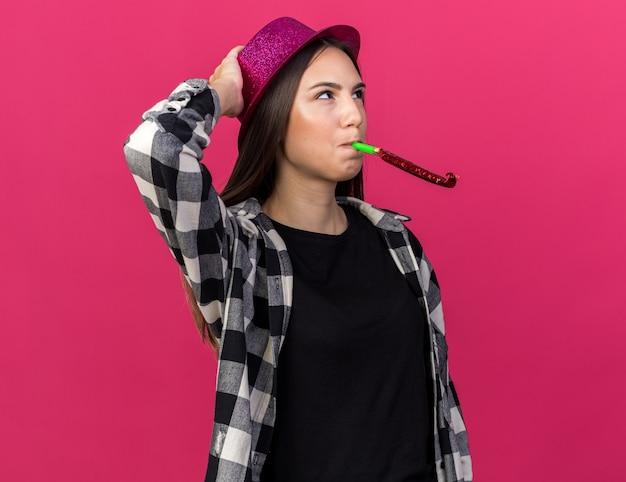Zadowolona młoda piękna kobieta nosząca imprezowy kapelusz dmuchający gwizdek kładący rękę na głowie