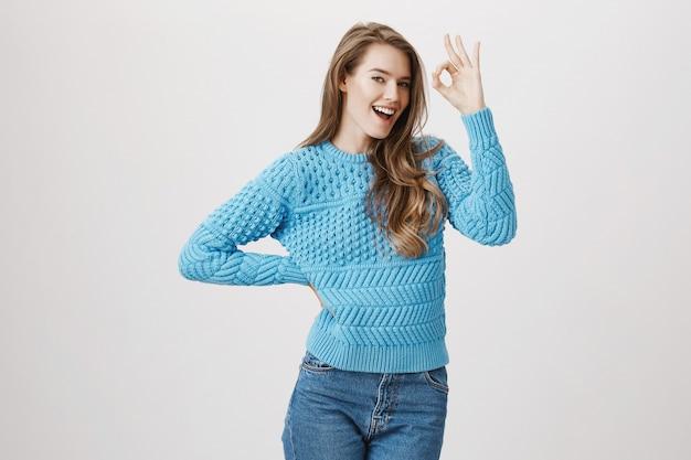 Zadowolona młoda piękna kobieta pokazuje znak w porządku