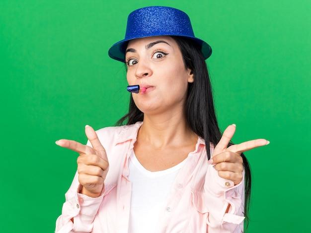 Zadowolona młoda piękna kobieta w kapeluszu imprezowym dmuchająca punkty gwizdka z przodu na zielonej ścianie
