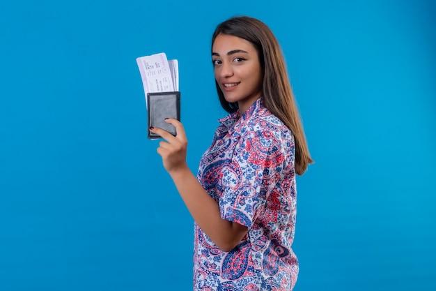 Zadowolona młoda piękna podróżna kobieta stojąca z biletami i paszportem, pewnie uśmiechnięta stojąca na niebieskim tle