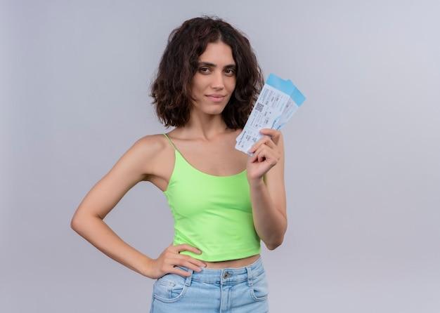 Zadowolona młoda piękna podróżniczka kobieta trzyma bilety lotnicze na na białym tle białej ścianie