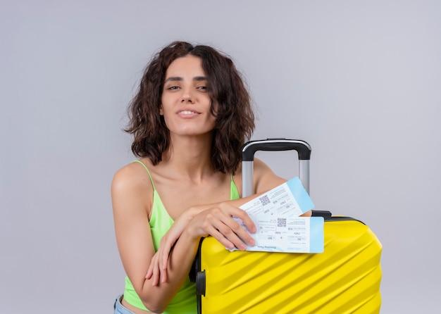 Zadowolona młoda piękna podróżniczka posiadająca bilety lotnicze i walizkę na na białym tle białej ścianie