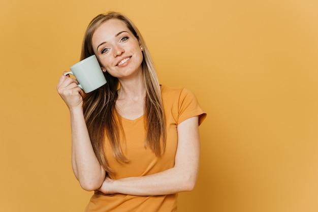 Zadowolona młoda piękna ruda kobieta w pomarańczowej koszulce z uroczym uśmiechem w romantycznym nastroju