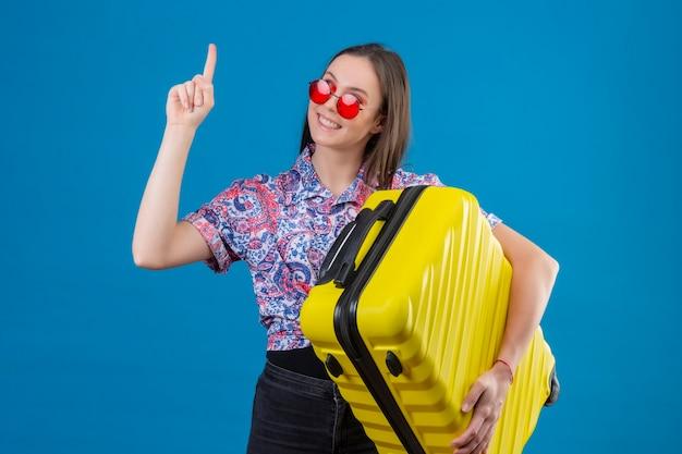 Zadowolona młoda podróżniczka kobieta ubrana w czerwone okulary przeciwsłoneczne, trzymając żółtą walizkę stojąc z palcem w górę patrząc pewnie, że ma świetny pomysł na niebieskim tle