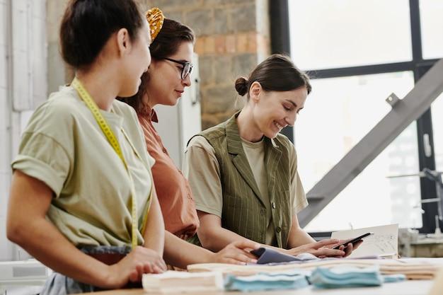 Zadowolona młoda projektantka mody ze smartfonem, która pokazuje swoim kolegom nowe elementy z sezonowej kolekcji i omawia je