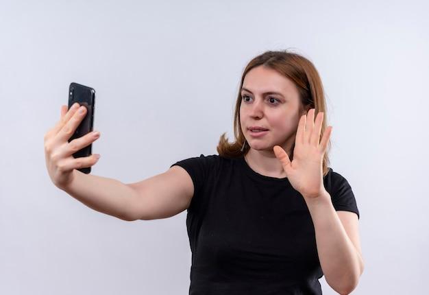 Zadowolona młoda przypadkowa kobieta trzyma telefon komórkowy i gestykuluje cześć przy telefonie na odosobnionej białej przestrzeni