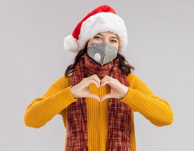 Zadowolona młoda słowiańska dziewczyna w czapce świętego mikołaja i szaliku na szyi, ubrana w maskę medyczną, gestykulując znak serca na białym tle na białej ścianie z miejscem na kopię