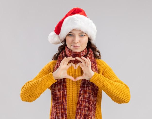 Zadowolona młoda słowiańska dziewczyna w czapce świętego mikołaja i szaliku wokół szyi, gestykulując znak serca na białym tle na białej ścianie z miejsca na kopię