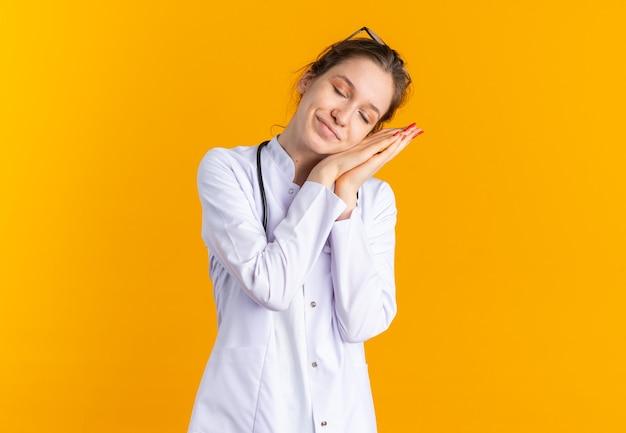 Zadowolona młoda słowiańska dziewczyna w mundurze lekarza ze stetoskopem, kładąc głowę na dłoniach, odizolowana na pomarańczowej ścianie z miejscem na kopię