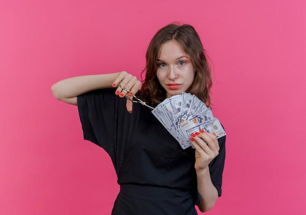 Zadowolona młoda słowiańska fryzjerka w mundurze, trzymająca pieniądze i nożyczki, próbująca wyciąć pieniądze na różowym tle z miejscem na kopię