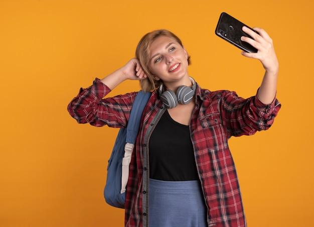 Zadowolona młoda słowiańska studentka ze słuchawkami w plecaku kładzie rękę na głowie, trzymając i patrząc na telefon