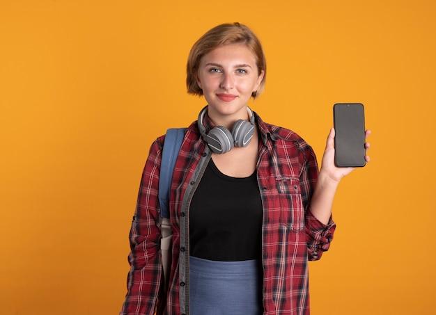 Zadowolona młoda słowiańska studentka ze słuchawkami w plecaku trzyma telefon