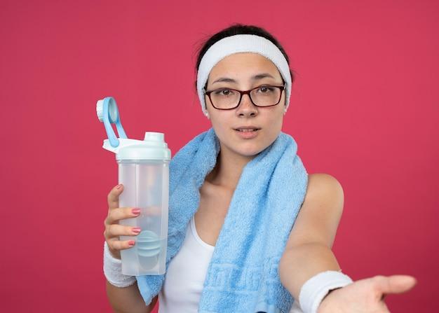 Zadowolona młoda sportowa dziewczyna w okularach optycznych z ręcznikiem na szyi nosząca opaskę i opaski na rękę trzymając butelkę wody i wyciągając rękę