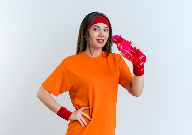 Zadowolona młoda sportowa kobieta ubrana w opaskę i opaski na rękę, trzymając butelkę wody, trzymając rękę na talii na białym tle na białej ścianie z miejscem na kopię