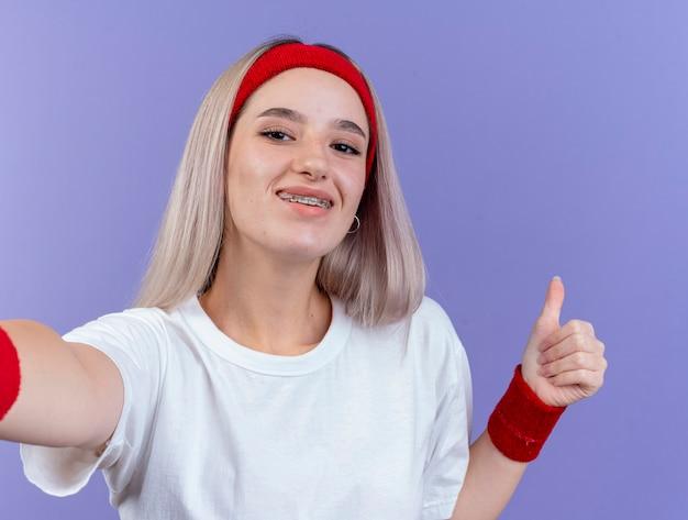 Zadowolona młoda sportowa kobieta z szelkami, nosząca opaskę i opaski na nadgarstek, kciuki do góry i patrzy na przód odizolowany na fioletowej ścianie