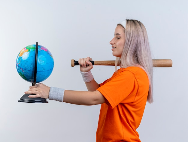 Zadowolona młoda sportowa kobieta z szelkami, nosząca opaskę i opaski na nadgarstek, stoi bokiem, trzymając kij baseballowy i kula ziemska na białej ścianie