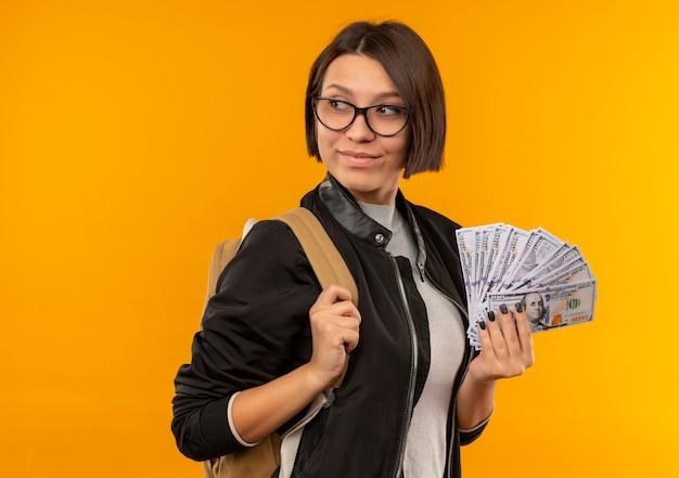 Zadowolona młoda studentka w okularach iz powrotem trzymając pieniądze, patrząc na bok na białym tle na pomarańczowej ścianie